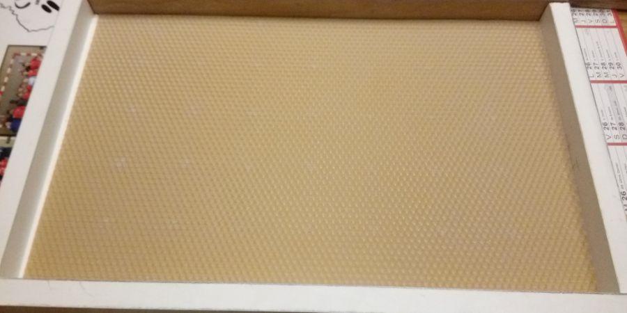Les bords du gaufrier sont fixés et la feuille de cire qui va servir de matrice